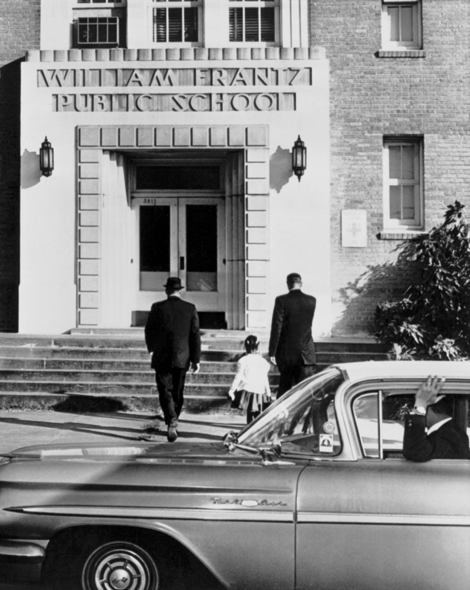 Ruby Bridges is escorted by US Federal Marshals into William Frantz elementary school.