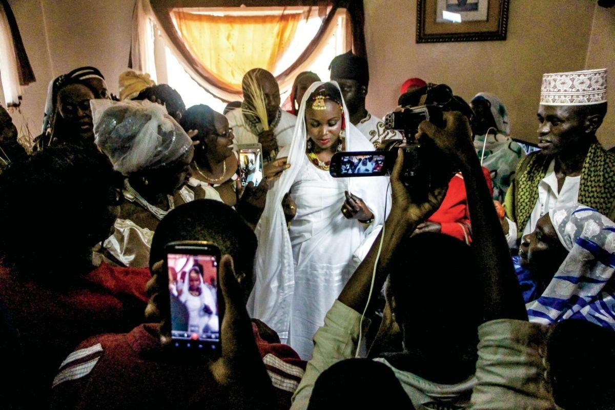 A bride is surrounded by friends and family in her parent's living room in Kibera