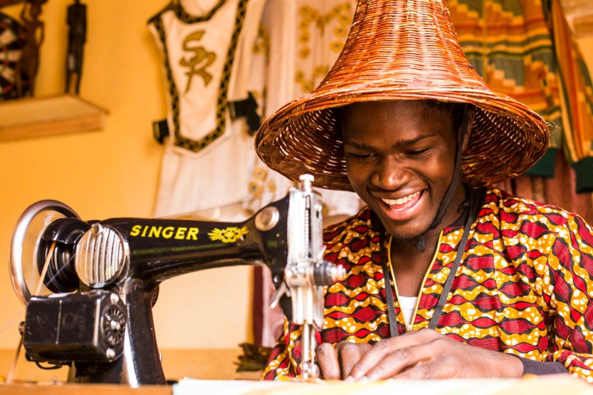 Designer David Ochieng uses singer sewing machine to stitch together threads