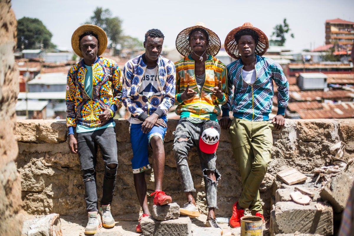 Four men pose in zip-ups with African fabric
