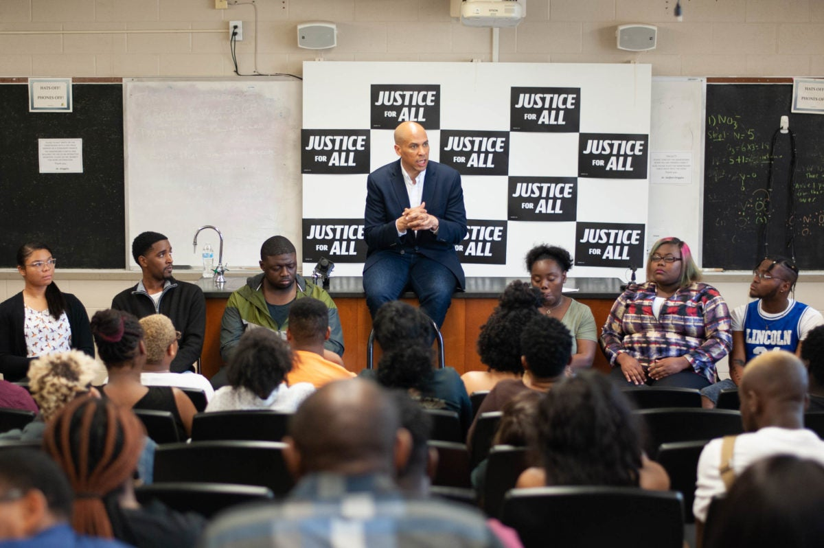 Presidential candidate Cory Booker sits in front of a classroom