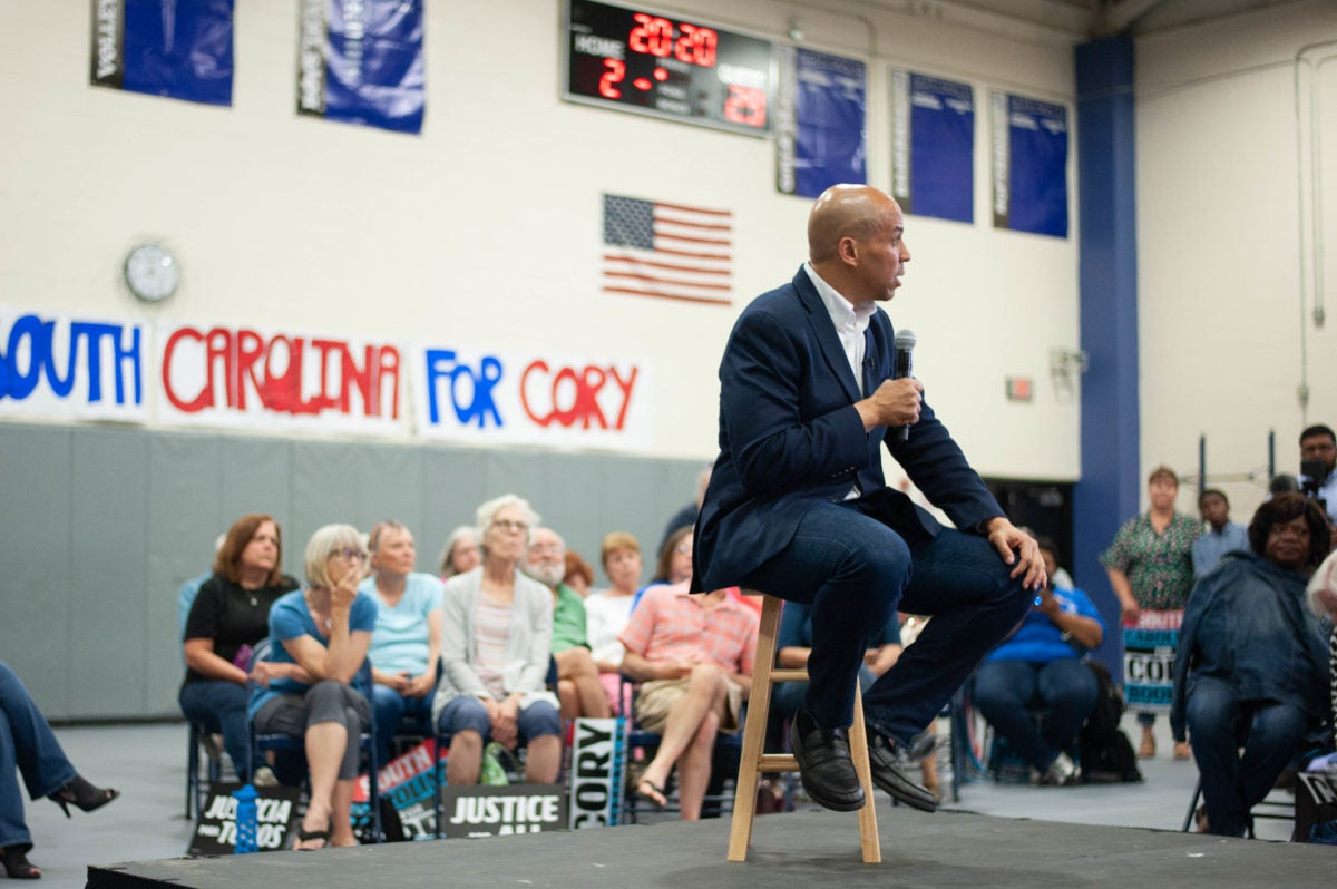 Presidential candidate Cory Booker sits on a stool in a gymnasium and talks to attendees