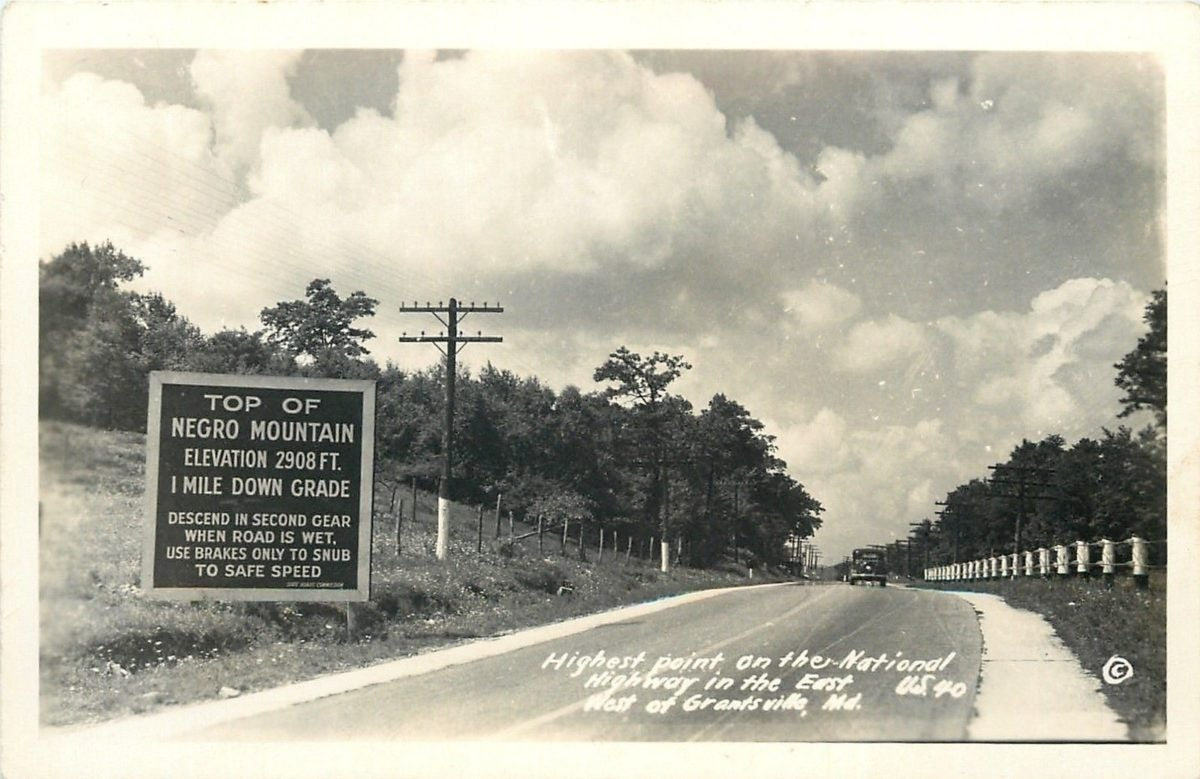 "An old postcard depicts the words ""Negro Mountain"" on a state highway sign."
