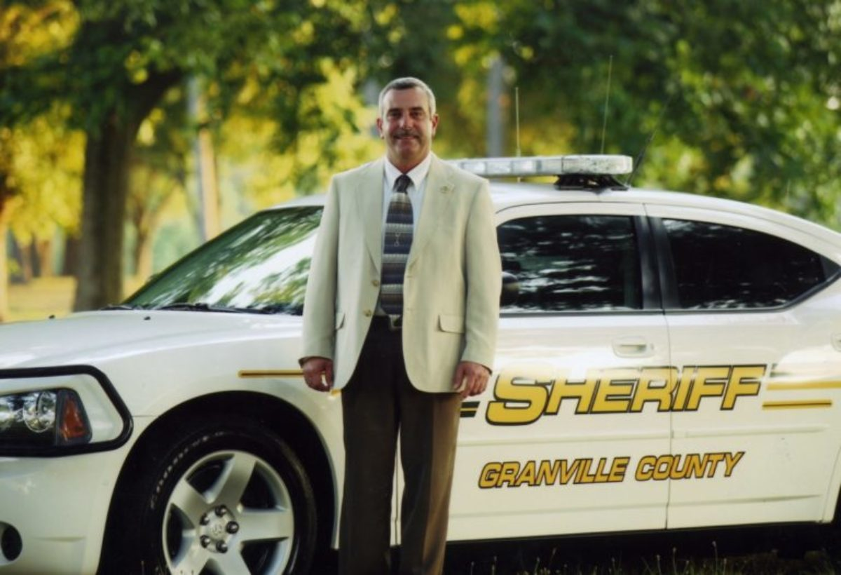 Sheriff Brindell Jenkins stands in front of a Granville County police car.
