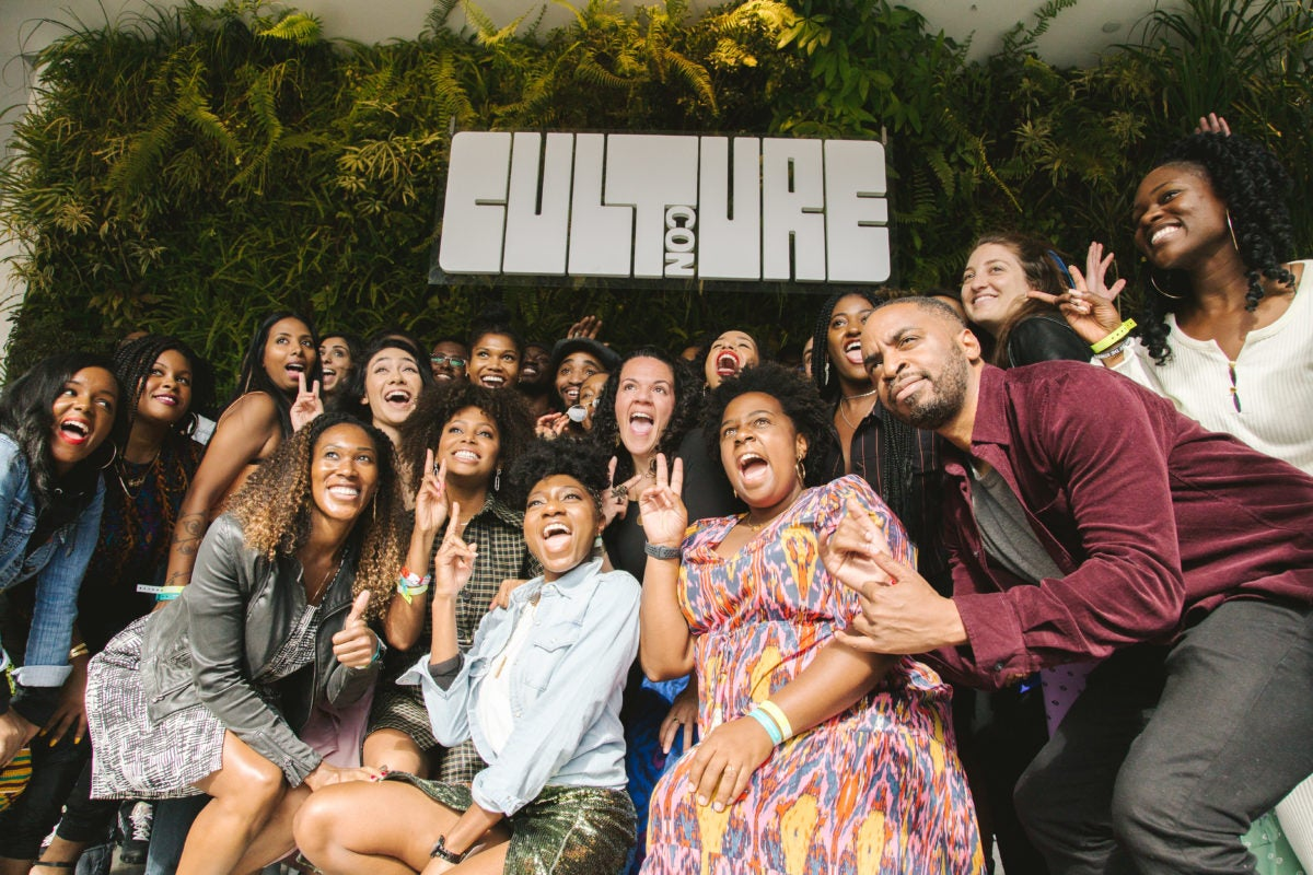 A group of Black creatives pose for a photo in front of CultureCon signage