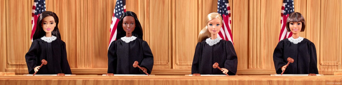 Judge Barbie sits behind a bench and in front of an American flag