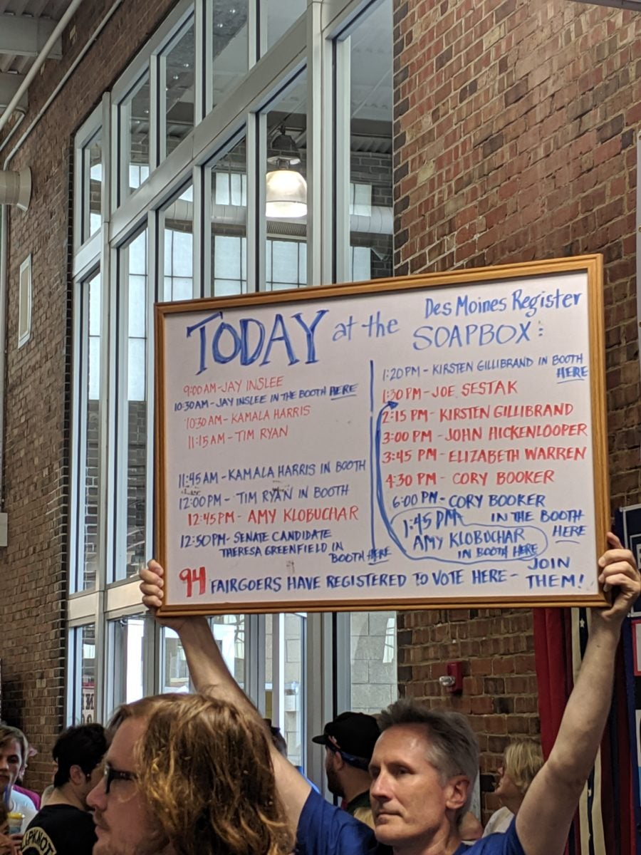 Man holds up sign at Iowa State Fair announcing times for candidates to appear at Democratic booth
