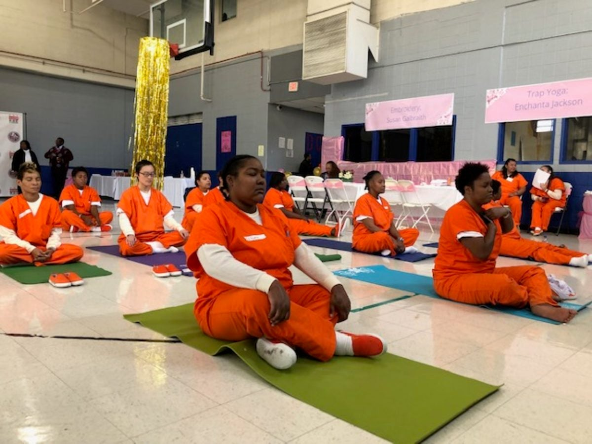 women participate in trap yoga at DCDOC's empowerment event