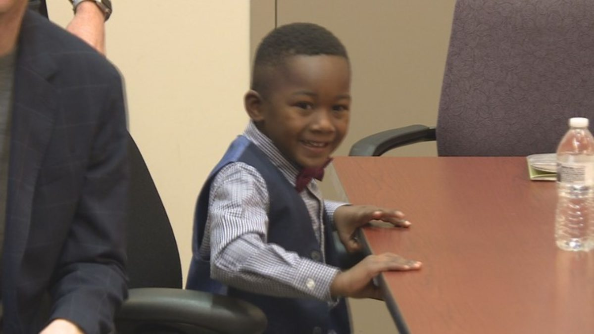 Michael Orlando Clark Jr. sits at the legal hearing for his adoption.