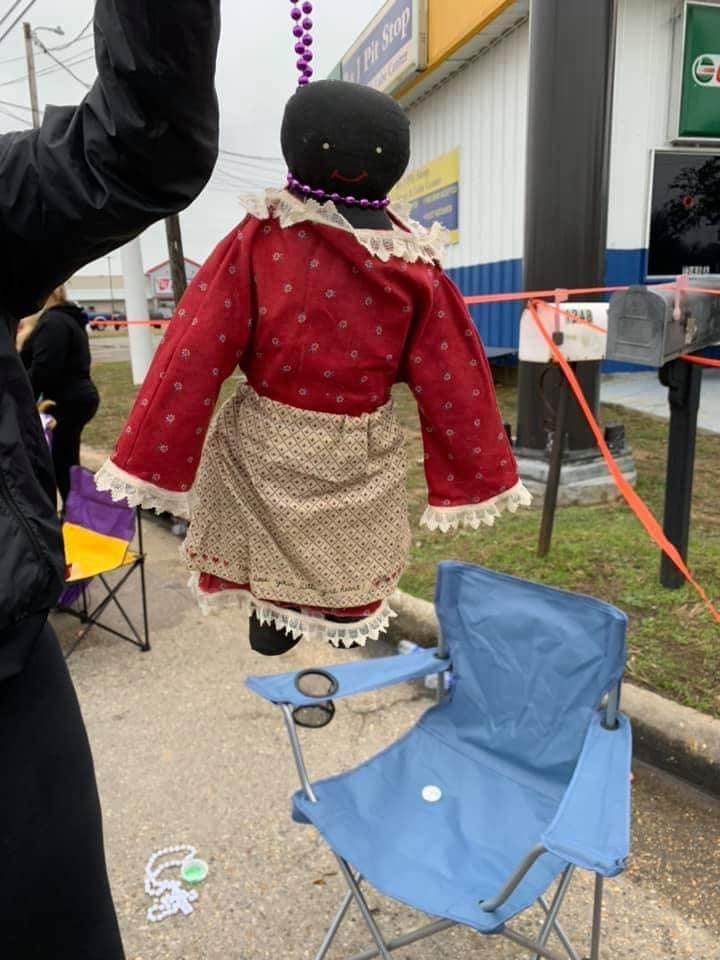 Black Doll Hanging From Noose Made Of Beads Given To Child During Mardi Gras Parade