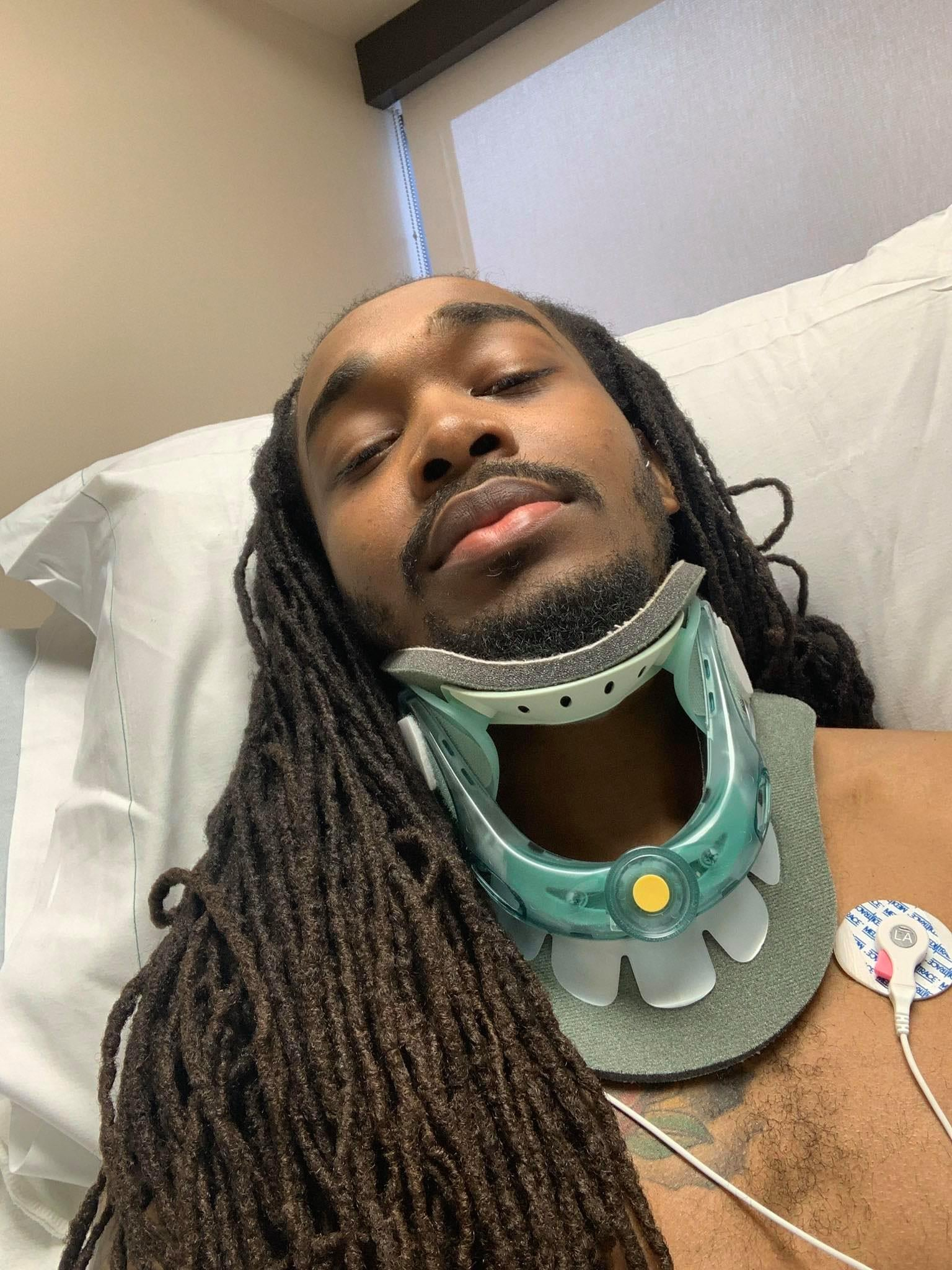 Jeremiah Cribb lays in a hospital bed with a neck brace