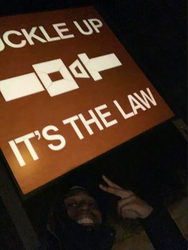 "Jaylan Butler stops to take a photo near a road sign that says ""Buckle Up It's The Law"""
