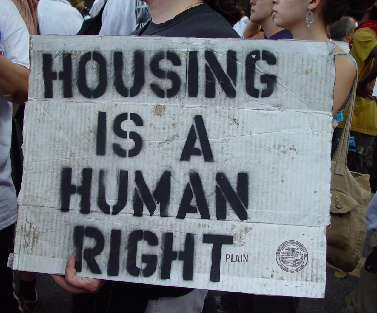 "Someone holds ""Housing Is A Human Right"" poster in support of Love Beyond Walls"