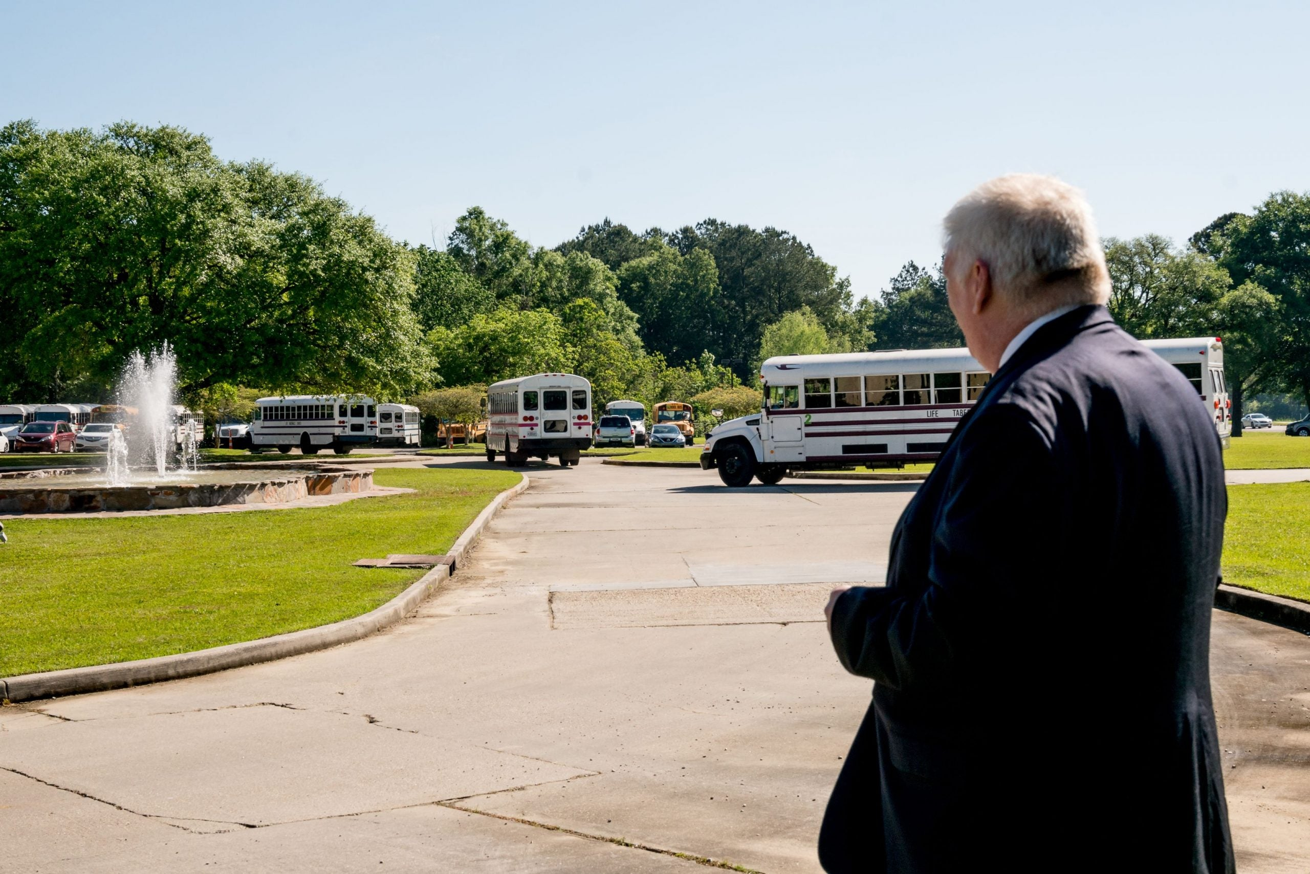 Joe Long, an attorney working with Pastor Tony Spell, watches as buses bring congregation members to Life Tabernacle Church for a Palm Sunday service in Baton Rouge, Louisiana