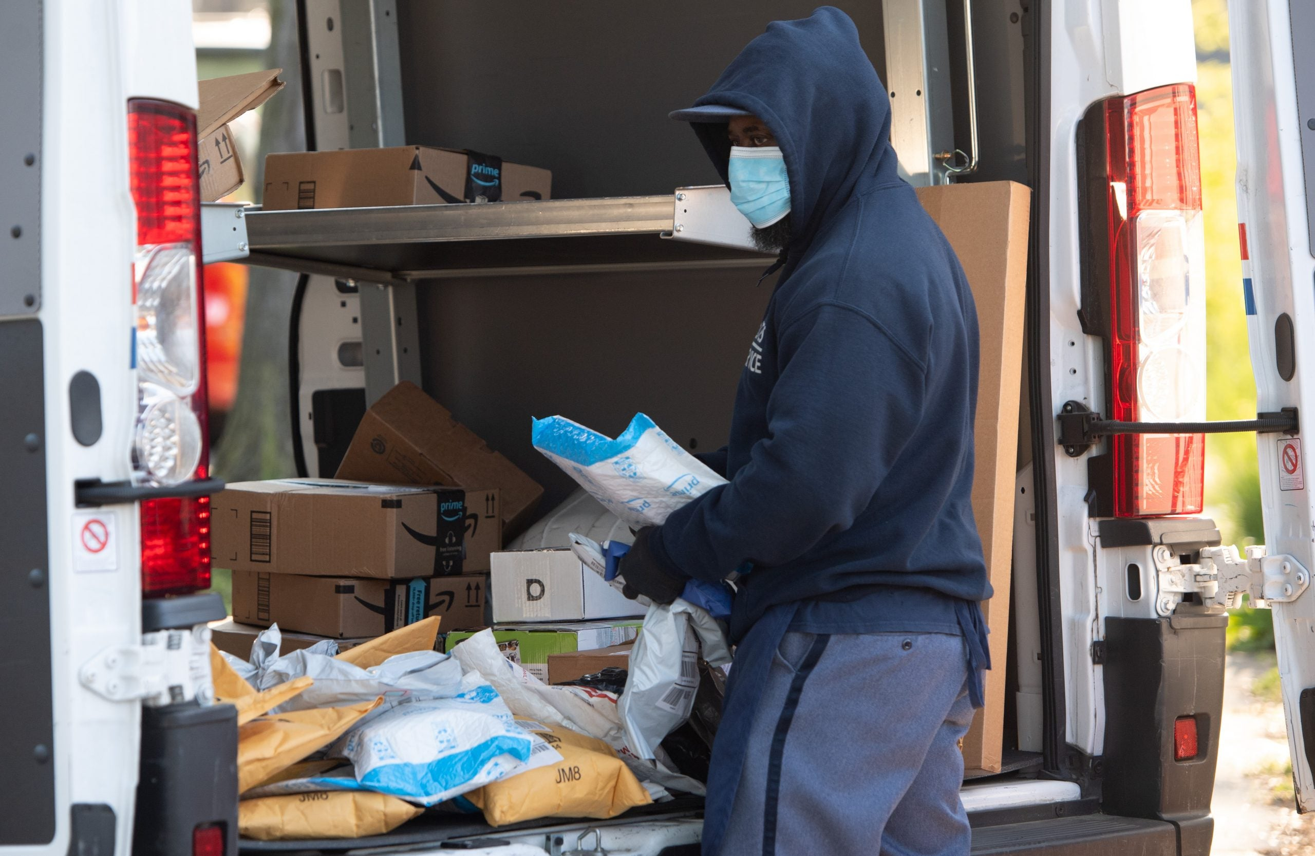 A mailman wearing a mask and gloves to protect himself and others from COVID-19, known as coronavirus, loads a postal truck with packages at a United States Postal Service