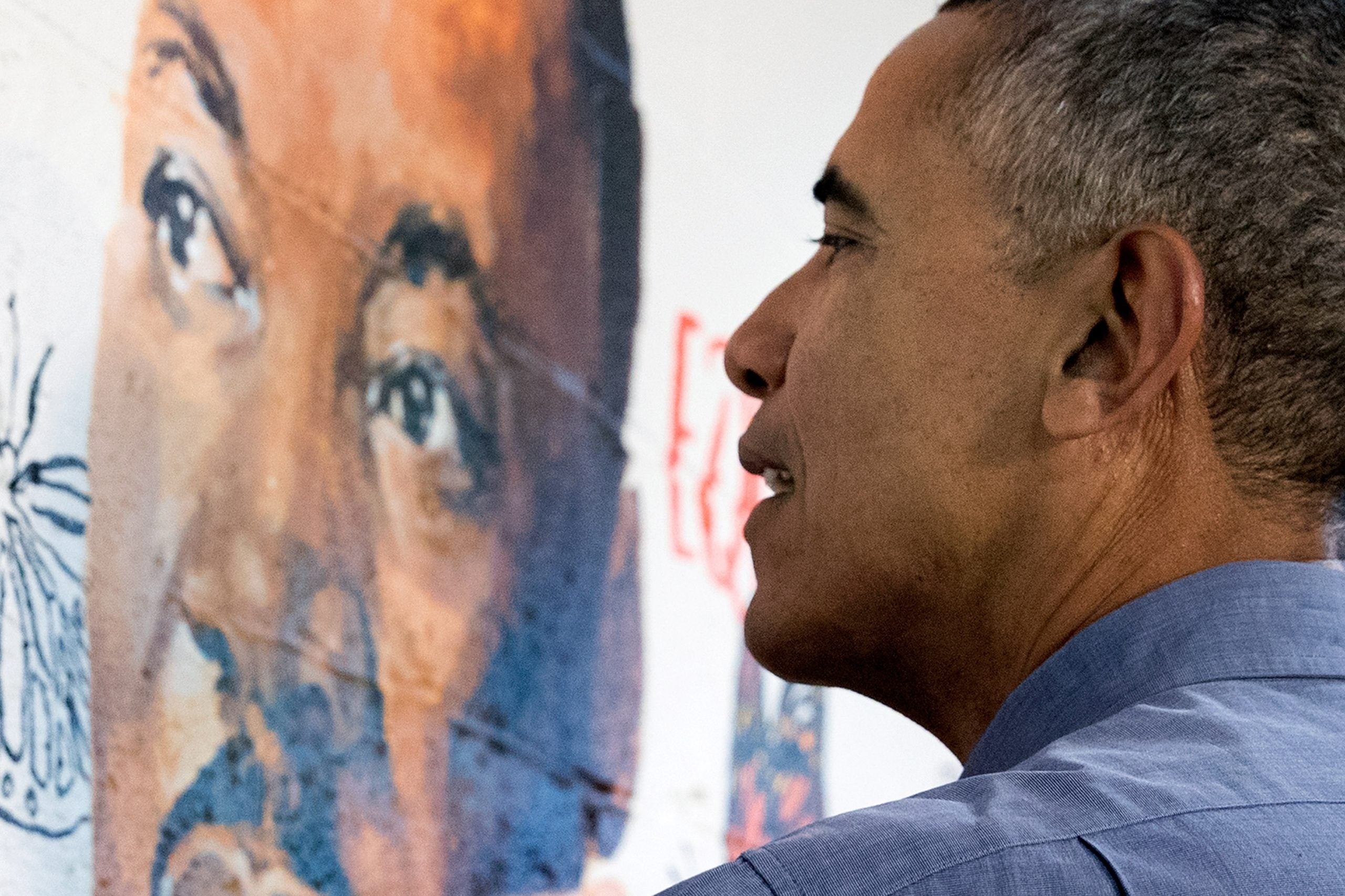 President Barack Obama helps paint a mural depicting Martin Luther King Jr., at the Jobs Have Priority Naylor Road Family Shelter
