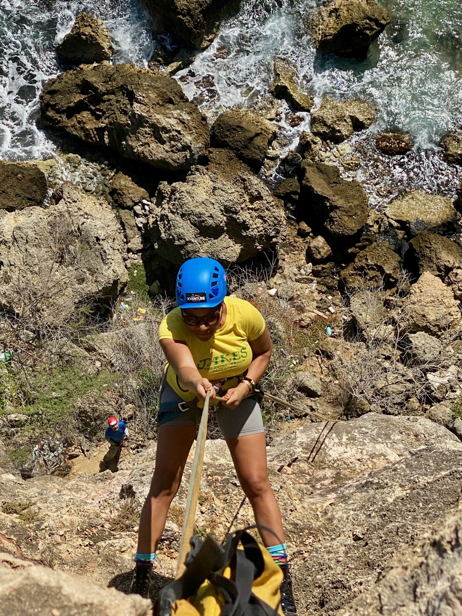 Travel expert rock climbs in Curacao