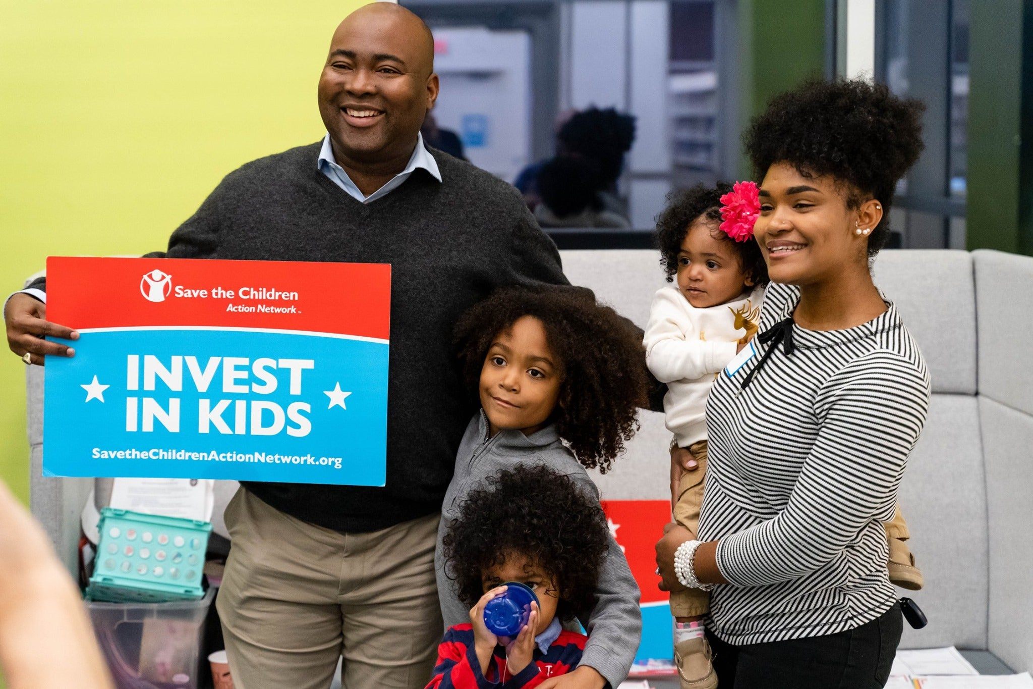 "Jaime Harrison poses with kids holding an ""Invest in Kids"" sign"