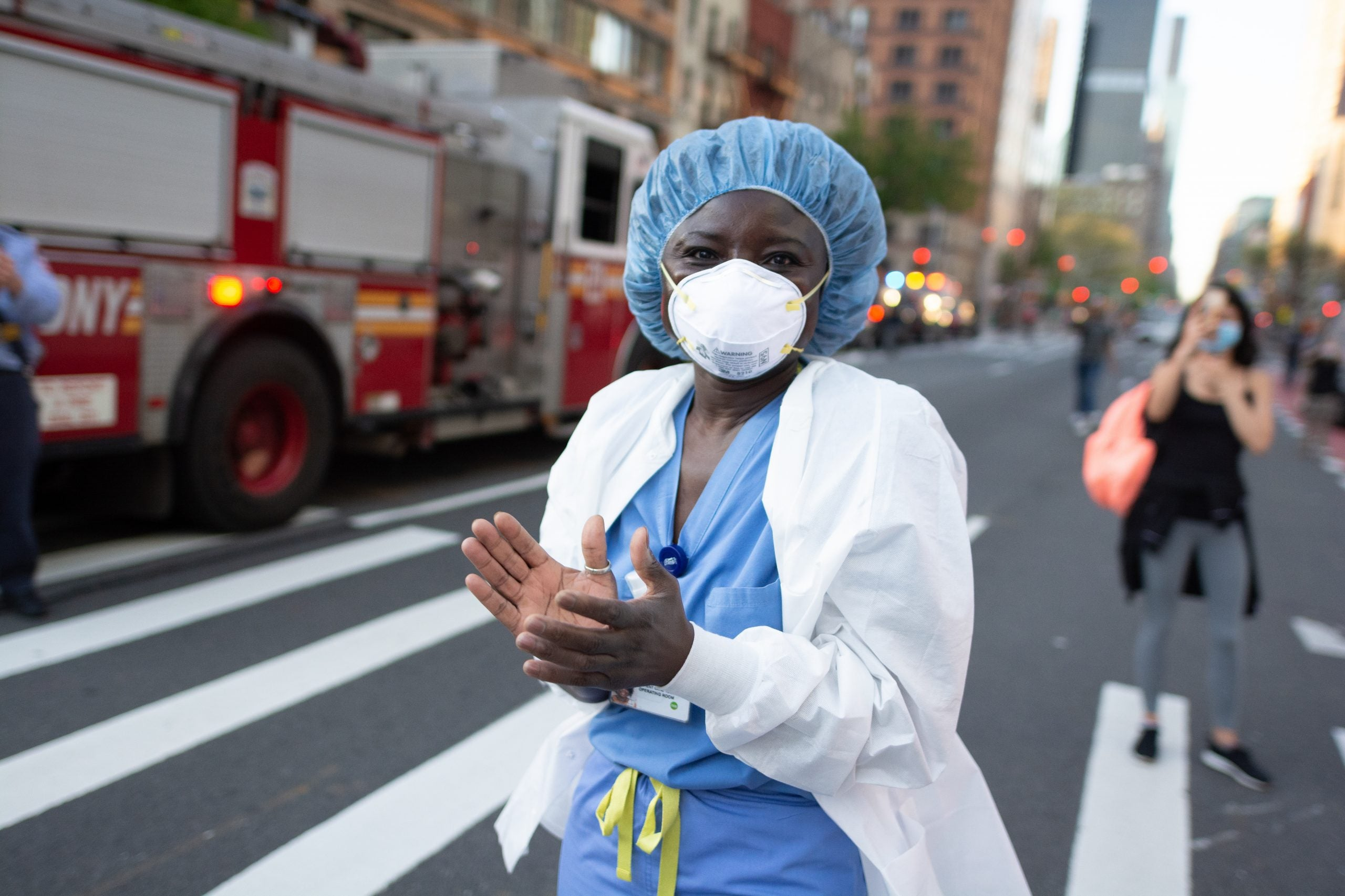 NEW YORK, UNITED STATES - 2020/05/03: A medical worker applauds along with the crowd outside the NYU Langone Medical Center in Manhattan amid the coronavirus pandemic. New York City continues to see a decrease in hospitalizations, a sign that confinement and social distancing measures have been effective. (Photo by Braulio Jatar/SOPA Images/LightRocket via Getty Images)