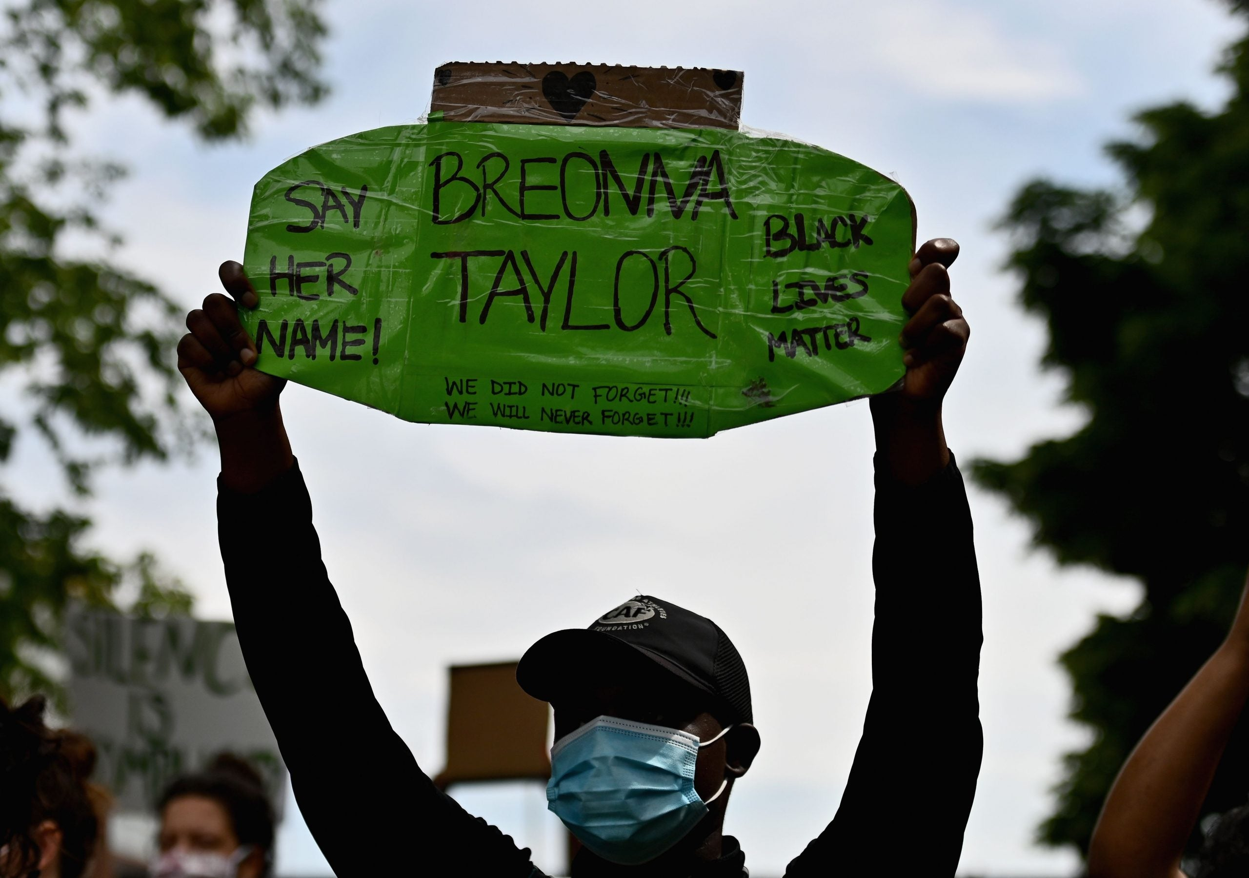 Protester holds sign remembering Breonna Taylor following her death at the hands of Brett Hankinson and two additional officers