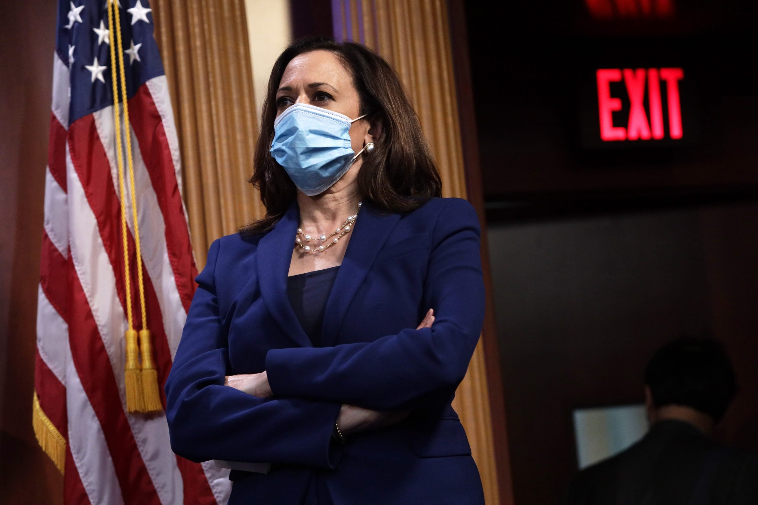 Kamala Harris stands with arms folded wearing a mask