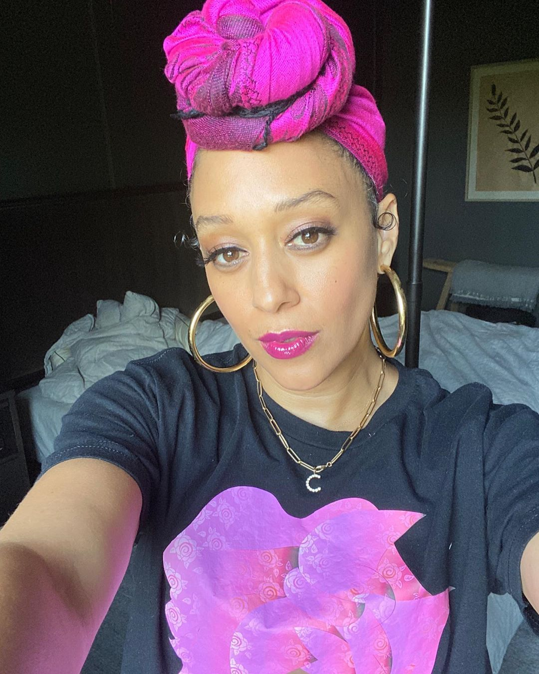 Tia Mowry in pink headwrap and black shirt