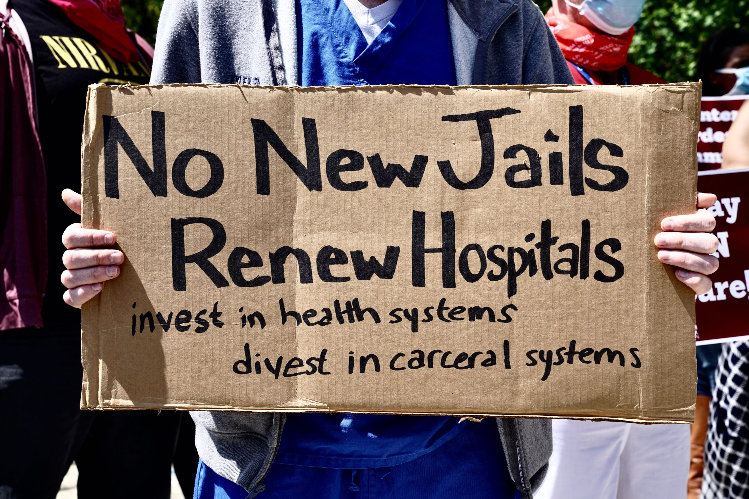 A health worker holds a sign during a nurses protest at Rikers Island Prison over conditions and COVID-19 threat