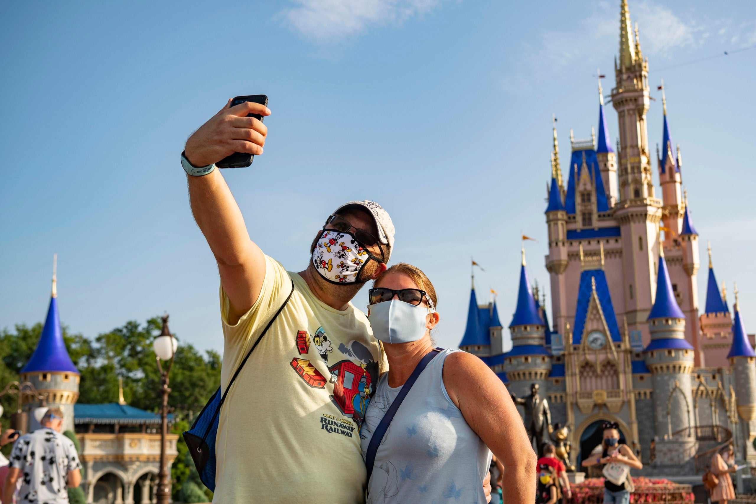 In this handout photo provided by Walt Disney World Resort, guests stop to take a selfie at Magic Kingdom Park at Walt Disney World Resort on July 11, 2020 in Lake Buena Vista, Florida. July 11, 2020 is the first day of the phased reopening. (Photo by Matt Stroshane/Walt Disney World Resort via Getty Images)