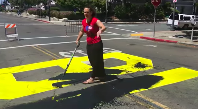 """The woman painted over the """"B"""" and the """"L"""" of the Black Lives Matter mural in Martinez, California"""