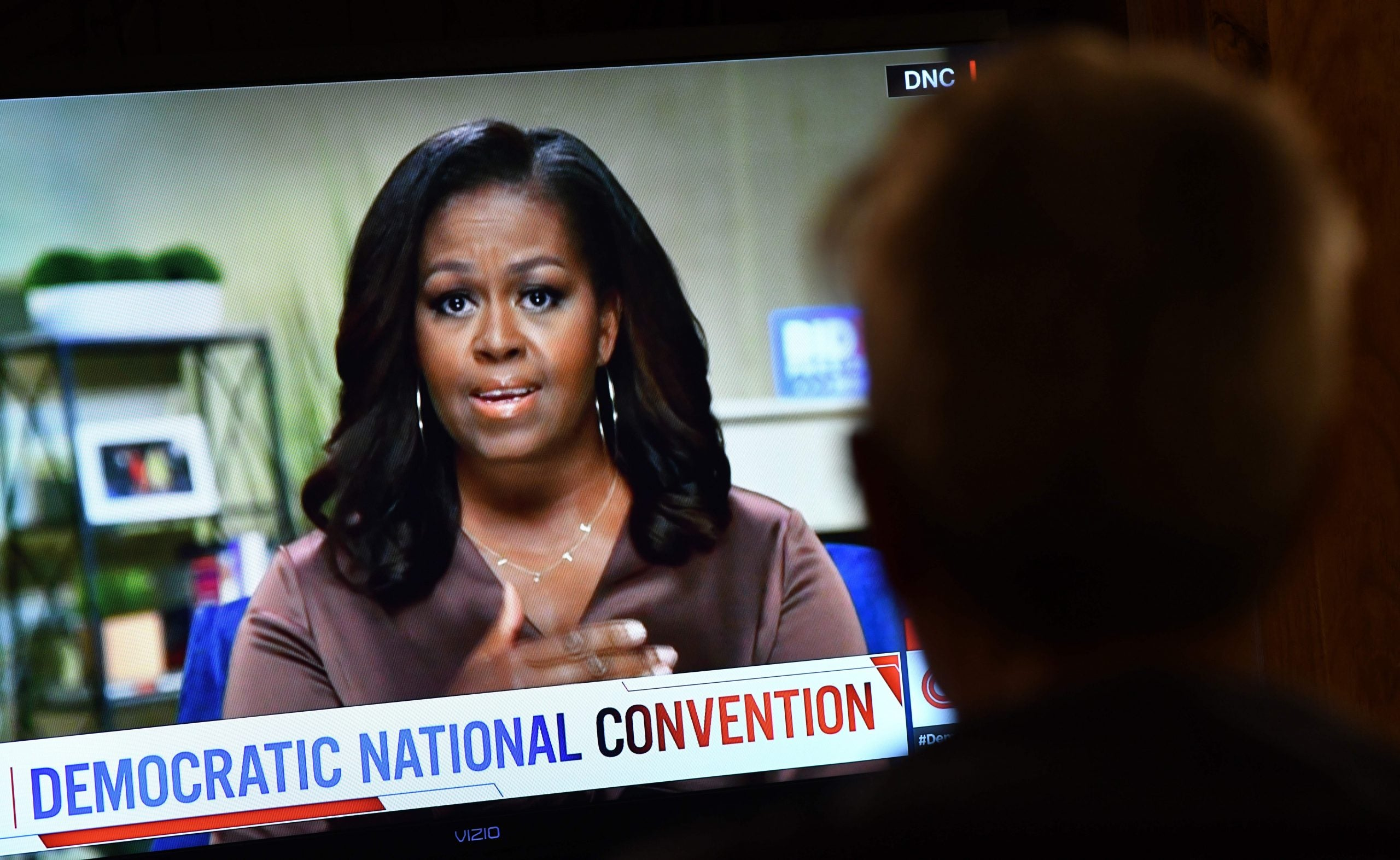 A person watches former First Lady Michelle Obama speak during the opening night of the Democratic National Convention, being held virtually amid the novel coronavirus pandemic, in Los Angeles, on August 17, 2020. - (Photo by CHRIS DELMAS/AFP via Getty Images)