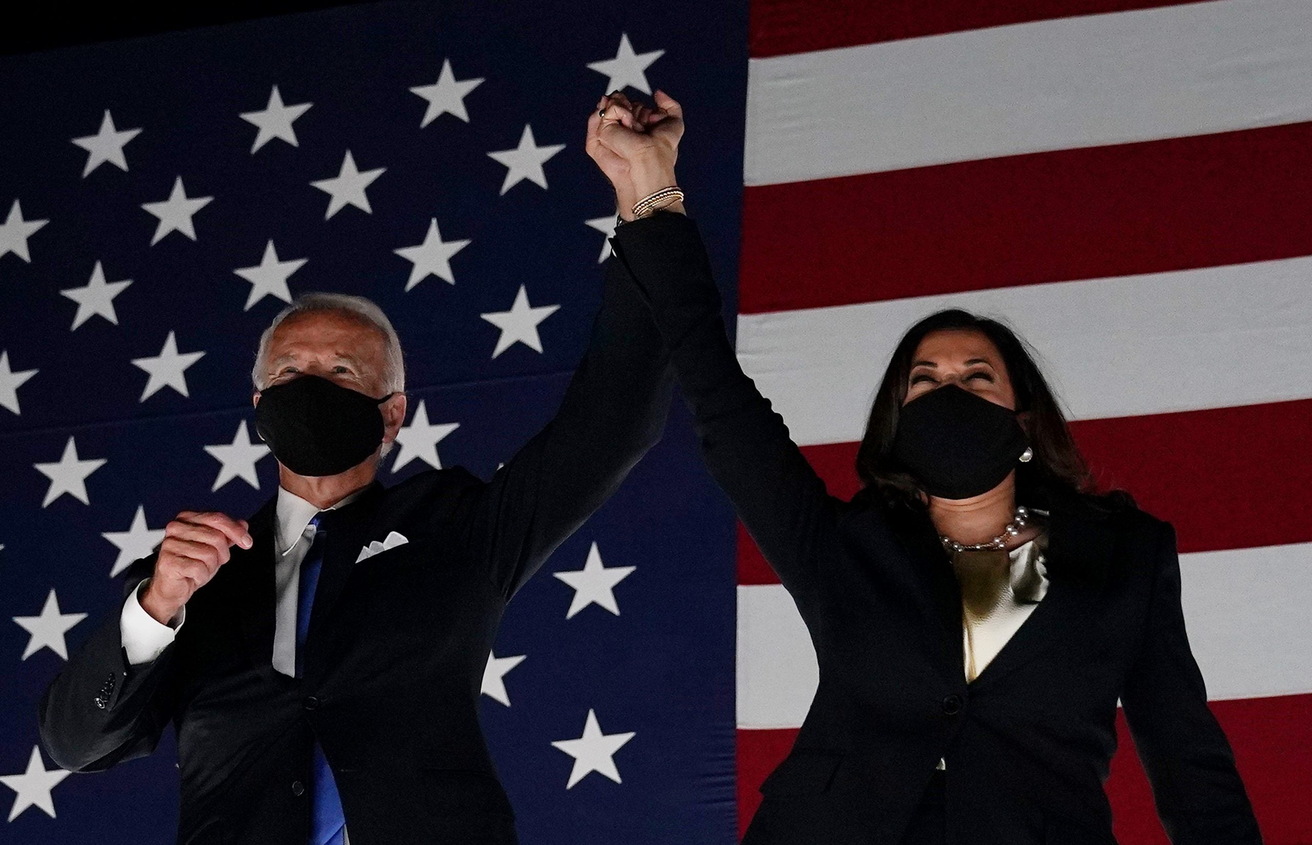 Kamala Harris and Joe Biden clasp hands in front of an American flag to formalize Biden-Harris ticket