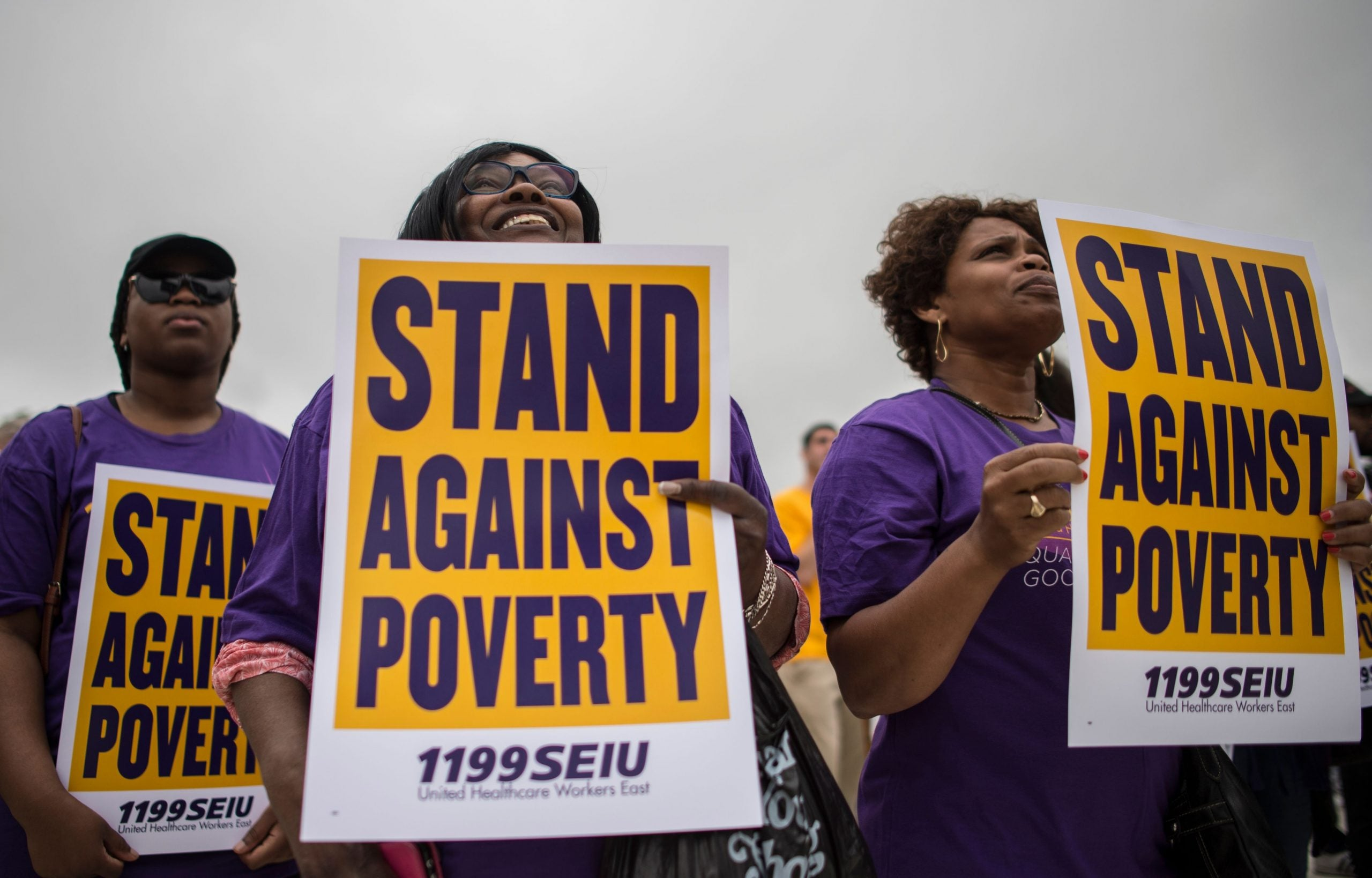 protestors at Poor People's Campaign rally hold signs addressing poverty