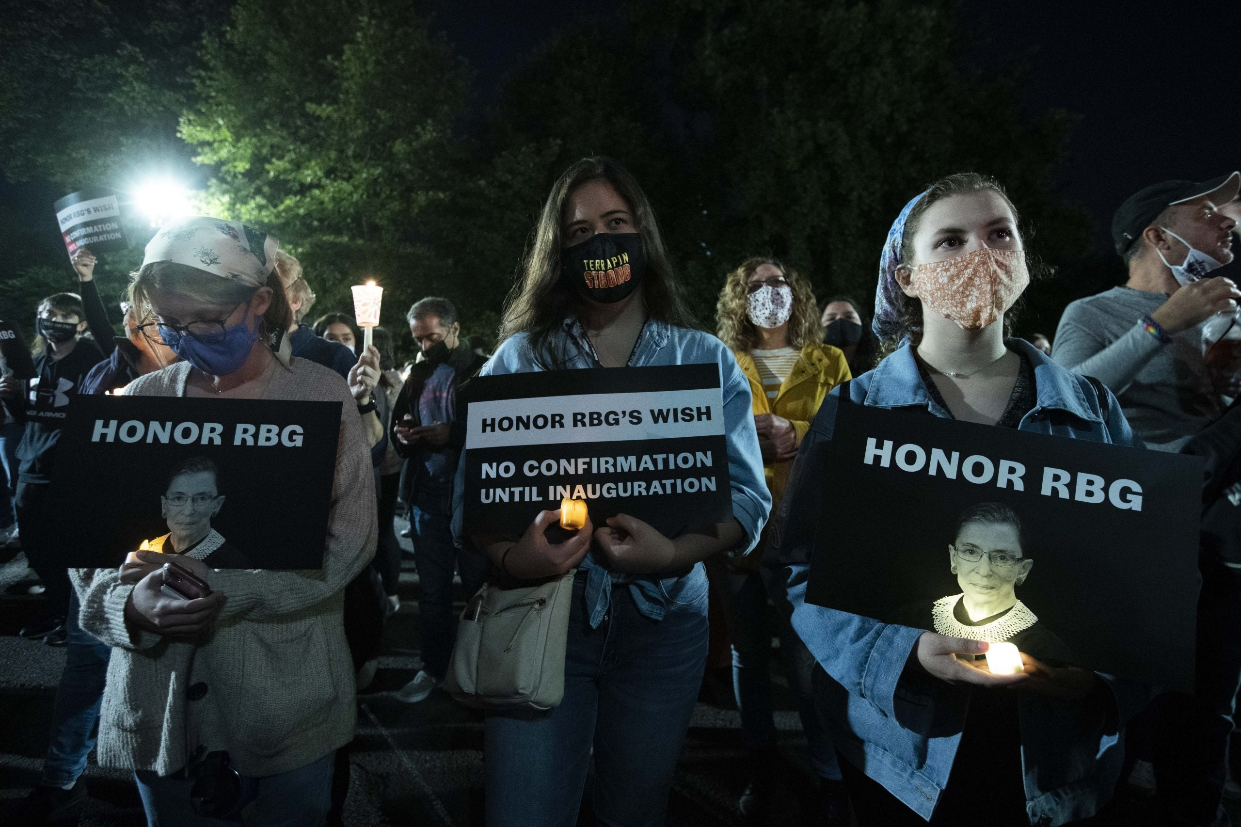 People hold signs and candles as they pay their respects to Ruth Bader Ginsburg near the US Supreme Court in Washington, DC on September 19, 2020. - US President Donald Trump vowed to quickly nominate a successor, likely a woman, to replace late Supreme Court Justice Ruth Bader Ginsburg, only a day after the death of the liberal stalwart. (Photo by Jose Luis Magana / AFP) (Photo by JOSE LUIS MAGANA/AFP via Getty Images)